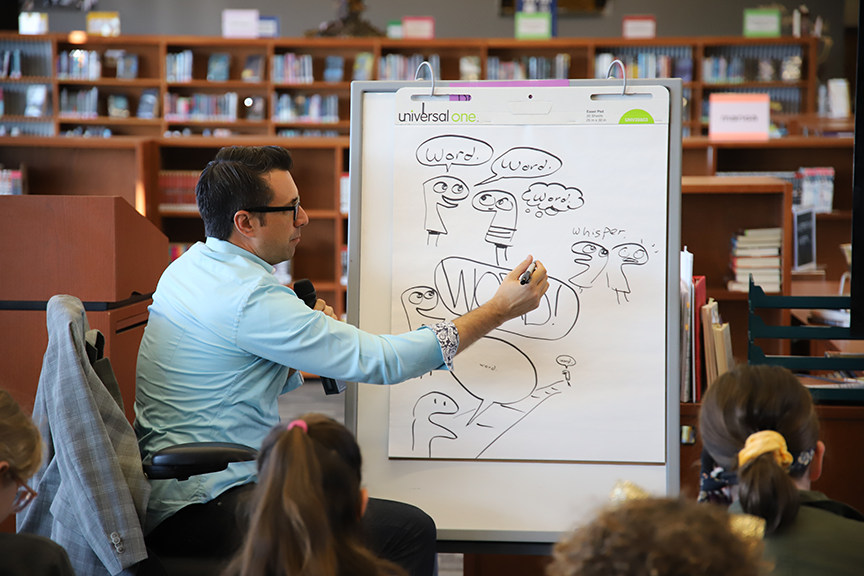 Jarrett J. Krosoczka drawing on a large sketchpad during his student workshop at FHS.